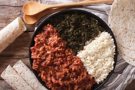 clarified: Ethiopian kitfo: marinated beef with herbs and cheese close-up on a plate and injera. horizontal view from above Stock Photo