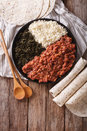 ethiopian: Ethiopian cuisine: kitfo with herbs and cheese on a plate and injera. vertical view from above
