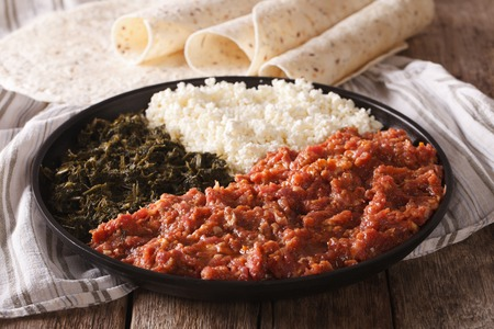 clarified: Ethiopian food kitfo: marinated beef with herbs and cheese close-up on a plate and injera. horizontal Stock Photo