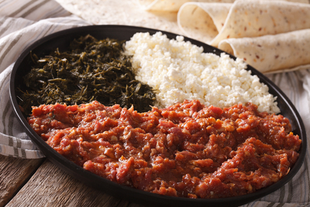 clarified: Ethiopian cuisine: kitfo with herbs and cheese on a plate and injera. Horizontal