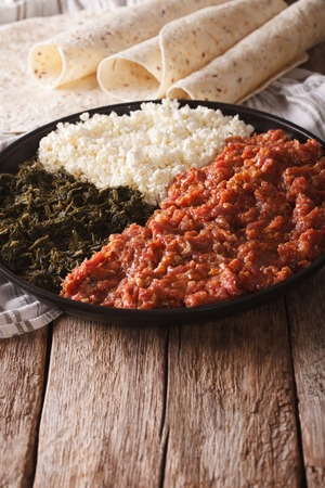 ethiopian: Ethiopian cuisine: kitfo with herbs and cheese on a plate and injera. Vertical