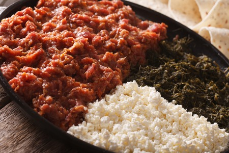 clarified: Ethiopian kitfo with herbs and cheese ayibe on a plate close-up. horizontal