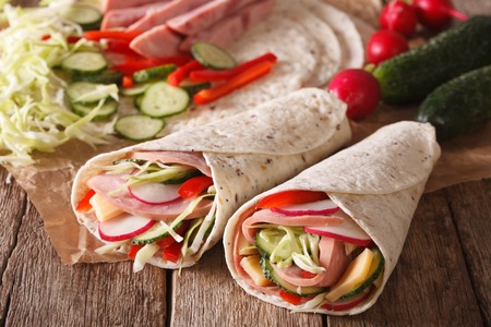 filled roll: Sandwich roll filled with ham, cheese and fresh vegetables close-up on the table. horizontal