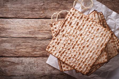 matzah: Jewish kosher matzah closeup on paper on a wooden table. horizontal view from above