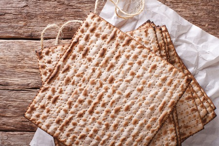 matzo: Jewish kosher matzo for Passover closeup on a wooden table. horizontal view from above Stock Photo