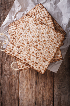 matzos: Jewish kosher matzah closeup on paper on a wooden table. vertical view from above