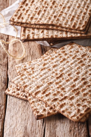 matzo: traditional Jewish kosher matzo for Passover macro on a wooden table. Vertical