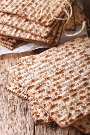 matzah: Jewish kosher matzah macro on a wooden table. Vertical