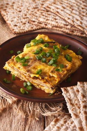 jewish cuisine: Jewish cuisine: matzah brei with green onions close-up on a plate. Vertical
