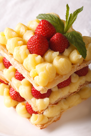 napoleon dessert: French cuisine: strawberry millefeuille with custard, decorated with mint, close-up. vertical
