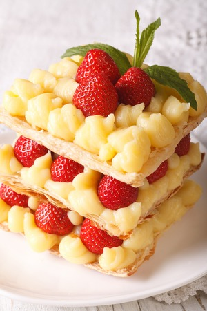 napoleon dessert: French dessert strawberry millefeuille with cream Patissiere close-up on a plate. vertical