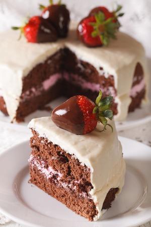 cake slice: piece of strawberry chocolate cake with white chocolate icing macro. vertical Stock Photo