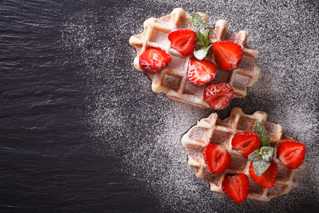 Liege waffles with fresh strawberries, powdered sugar close-up on the slate. Horizontal view from above Stockfoto
