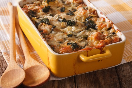 strata: Strata casserole with spinach, cheese and bread close up in a dish for baking. Horizontal