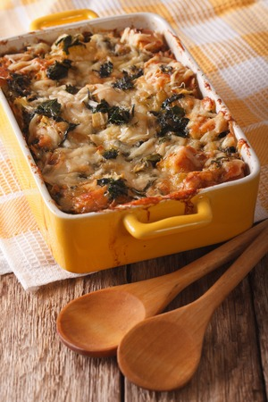 strata: Strata casserole with spinach, cheese and bread close up in a dish for baking. vertical Stock Photo