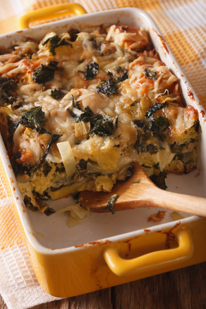 strata: Strata casserole with spinach close up in baking dish. vertical