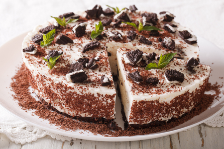 Cheesecake dessert with chunks of chocolate cookies decorated with mint close up on a plate. horizontal