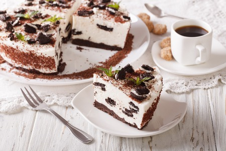 Beautiful dessert cheesecake with pieces of chocolate cookies close-up and coffee on the table. horizontal