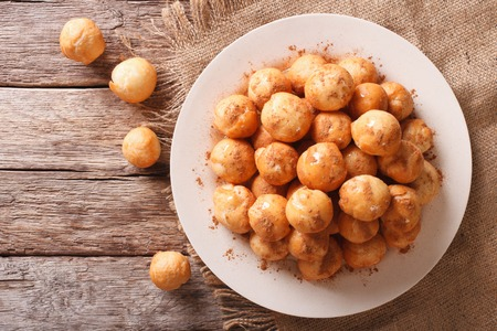 zeppole: loukoumades donuts with honey and cinnamon close-up on a plate. Horizontal view from above Stock Photo