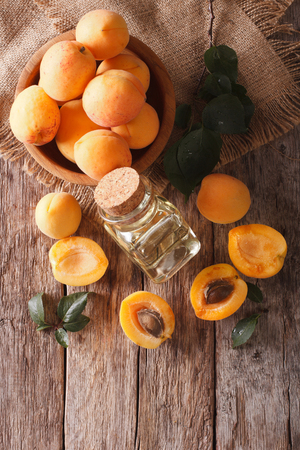 apricot kernel: apricot kernel oil in a glass jar closeup on the table and ingredients. Vertical view from above