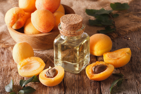 apricot kernel: apricot kernel oil in a glass jar closeup on the table and ingredients. Horizontal Stock Photo