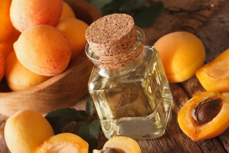 Healthy apricot oil in a glass bottle on a table macro. horizontal 免版税图像 - 60306182