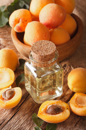 apricot kernel: apricot kernel oil in a glass jar closeup on the table. vertical Stock Photo