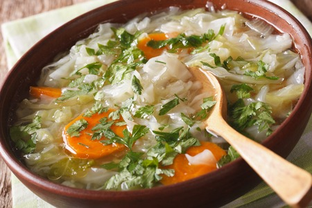 Diet soup with fresh cabbage close up in a bowl on the table. horizontal