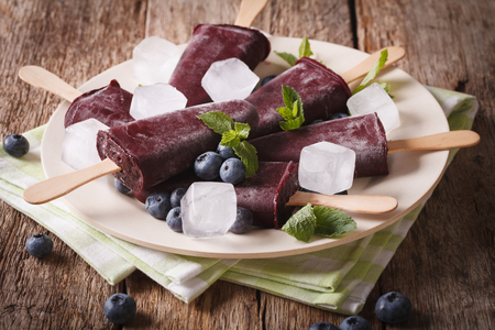 Homemade Blueberry ice cream on a stick closeup on a plate on the table. horizontal Stock Photo