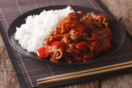 dinner menu: Pork braised in sweet and sour sauce with vegetables and rice close-up in an Asian style. horizontal Stock Photo