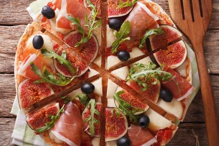 hams: Pizza en rodajas con higos, jamón, queso y primer plano de rúcula sobre una plancha de madera. Vista horizontal desde arriba