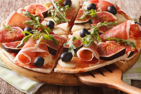 Sliced pizza with figs, ham, cheese and arugula close-up on a wooden board. horizontal