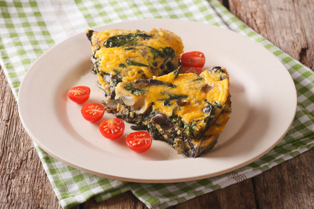 slices of frittata with spinach, cheese and mushrooms on a plate on a table close-up. horizontal