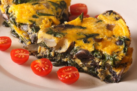 huevo blanco: Frittata with spinach and mushrooms on a plate close-up. horizontal