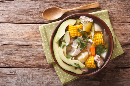 Traditional Colombian ajiaco soup close up in a bowl on the table. horizontal view from above Imagens