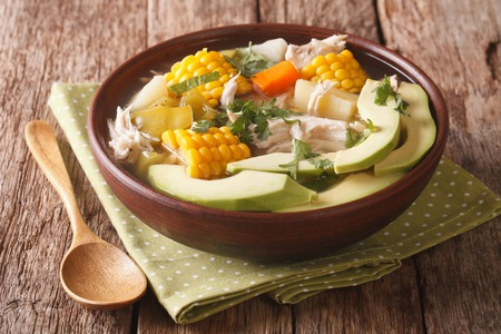 Colombian cuisine: ajiaco soup with chicken and vegetables close up in a bowl on the table. horizontal Standard-Bild