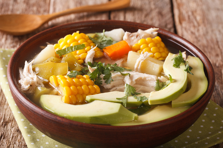 Tasty soup ajiaco with chicken and vegetables close up in a bowl on the table. horizontal