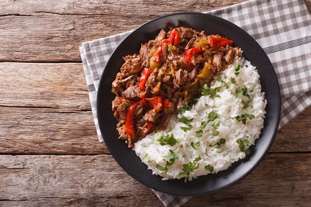 vieja: ropa vieja: beef stew in tomato sauce with vegetables and rice garnish on a plate close-up. horizontal view from above
