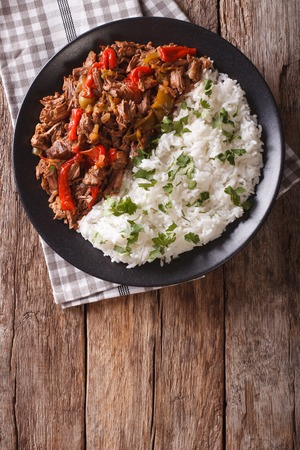 vieja: ropa vieja: beef stew in tomato sauce with vegetables and rice garnish on a plate close-up. vertical view from above