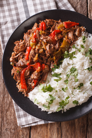 Cuban cuisine: ropa vieja meat with rice garnish on a plate  close-up. vertical view from above Stock Photo