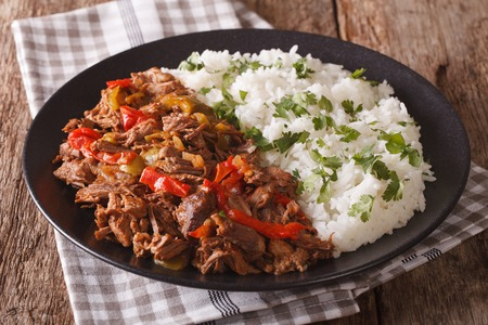 Mexican food ropa vieja: beef stew in tomato sauce with vegetables and rice garnish on a plate close-up. Horizontal
