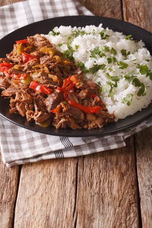 vieja: Mexican food ropa vieja: beef stew in tomato sauce with vegetables and rice garnish on a plate close-up. vertical Stock Photo