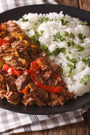vieja: ropa vieja: beef stew in tomato sauce with vegetables and rice garnish on a plate close-up. vertical