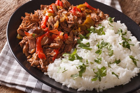 vieja: ropa vieja: beef stew in tomato sauce with vegetables and rice garnish on a plate macro. horizontal