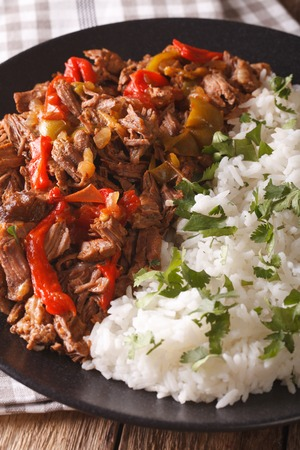vieja: Latin American cuisine: ropa vieja with rice close-up on a plate. vertical