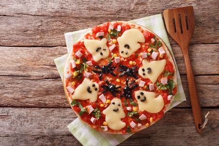 Halloween Food: Pizza with ghosts and spiders close-up on the table. horizontal view from above