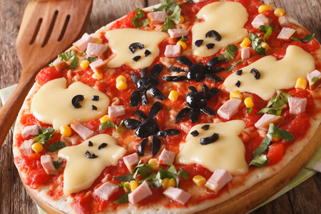 halloween pizza with cheese, olives, ham and ketchup close-up on the table. horizontal Standard-Bild