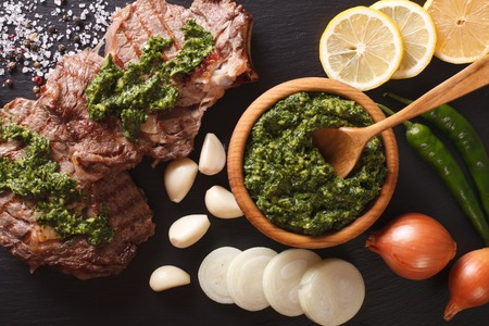 Argentine cuisine: grilled beef steak with chimichurri sauce macro on the table. horizontal view from above