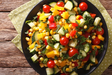 low  calorie: Low calorie salad of corn, tomatoes, cucumbers and pepper close-up on the table. Horizontal view from above
