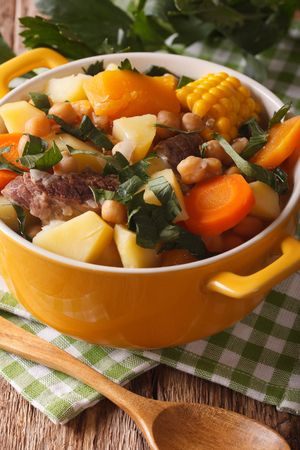 andalusian cuisine: South American cuisine: thick soup Pouchero close-up in a pot on the table. Vertical Stock Photo